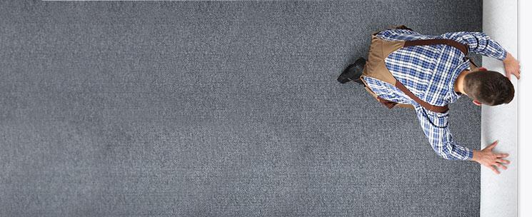 Carpet installer installing carpet